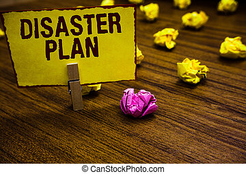 Writing note showing Disaster Plan. Business photo showcasing Respond to Emergency Preparedness Survival and First Aid Kit Clothespin holding yellow paper note crumpled papers several tries.
