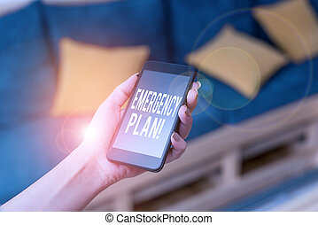 Writing note showing Emergency Plan. Business photo showcasing actions developed to mitigate damage of potential events woman using smartphone and technological devices inside the home.