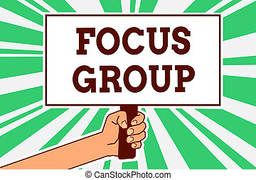 Writing note showing Focus Group. Business photo showcasing people assembled to participate in discussion about something Man hand holding poster important protest message green ray background.