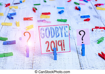 Writing note showing Godbye 2019. Business photo showcasing express good wishes when parting or at the end of last year Crumbling sheet with paper clips placed on the wooden table.