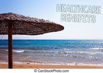 Writing note showing  Healthcare Benefits. Business photo showcasing it is insurance that covers the medical expenses Blue beach sand message idea sunshade water sky natural landscape.