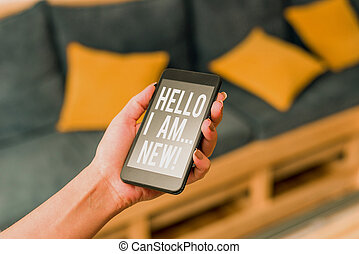 Writing note showing Hello I Am New. Business photo showcasing used as greeting or to begin telephone conversation woman using smartphone and technological devices inside the home.