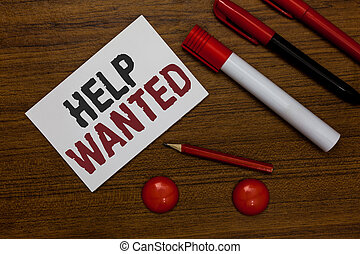 Writing note showing Help Wanted. Business photo showcasing advertisement placed in newspaper by employers seek employees White paper markers wooden background communicating ideas messages.