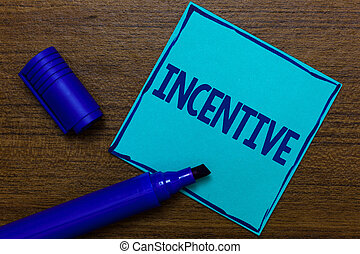 Writing note showing Incentive. Business photo showcasing thing that motivates or encourages someone to do something Blue Paper Important reminder Communicate ideas Wooden background.
