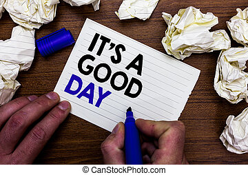Writing note showing It s is A Good Day. Business photo showcasing Happy time great vibes perfect to enjoy life beautiful Hand holding marker write words paper lob scatter around woody desk.
