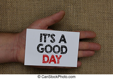 Writing note showing It s is A Good Day. Business photo showcasing Happy time great vibes perfect to enjoy life beautiful Human hand holding white page with black and red color texts on sack.
