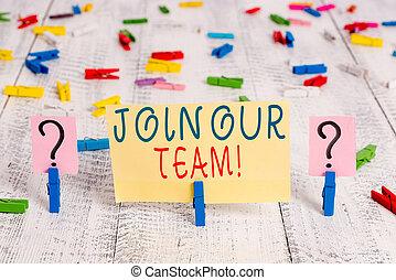 Writing note showing Join Our Team. Business photo showcasing invite someone to work together for particular purpose target Crumbling sheet with paper clips placed on the wooden table.