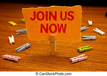 Writing note showing  Join Us Now. Business photo showcasing enroll community register website Recruit someone Sign-up Paperclip holding orange page show red text woody floor with clip.