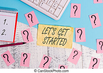 Writing note showing Lets Is Get Started. Business photo showcasing to begin doing or working on something you had started Writing tools and scribbled paper on top of the wooden table.