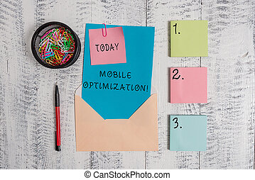 Writing note showing Mobile Optimization. Business photo showcasing Site Content Reformatted for Handheld or Tablet Devices Envelope letter sticky note ballpoint clips on wooden background.