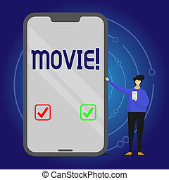 Writing note showing Movie. Business concept for Cinema or television film Motion picture Video displayed on screen Man Presenting Huge Smartphone while Holding Another Mobile