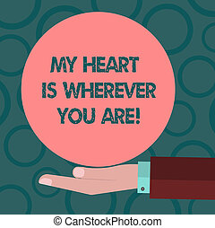 Writing note showing My Heart Is Wherever You Are. Business photo showcasing Expressing roanalysistic feelings and emotions Hu analysis Hand Offering Solid Color Circle Logo Posters.