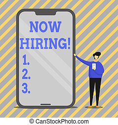 Writing note showing Now Hiring. Business photo showcasing finding evaluating working relationship with future employees Man Presenting Huge Smartphone while Holding Another Mobile.