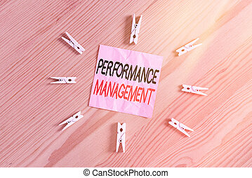 Writing note showing Performance Management. Business photo showcasing ongoing process of communication that occurs all year Colored clothespin papers empty reminder wooden floor background office.