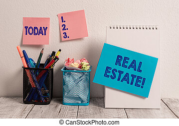 Writing note showing Real Estate. Business photo showcasing owning property consisting of empty land or buildings Sticky Notes Card on Wall Spiral Notebook 2 Mesh Pencil Pots Work Desk.
