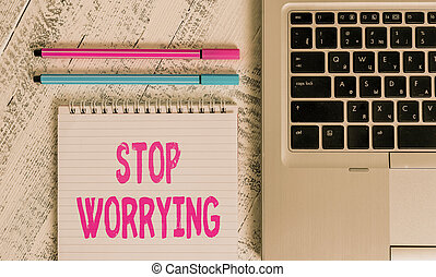 Writing note showing Stop Worrying. Business concept for stop thinking about something bad that happened in the past Metallic laptop blank ruled notepad pens lying old wooden vintage table