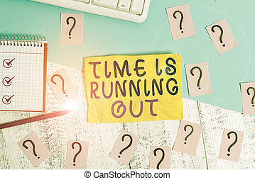 Writing note showing Time Is Running Out. Business photo showcasing Deadline is approaching Urgency things cannot wait Writing tools and scribbled paper on top of the wooden table.