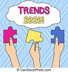 Writing note showing Trends 2020. Business photo showcasing general direction in which something is developing or changing Three Colored Empty Jigsaw Puzzle Pieces Held in Different People Hands.