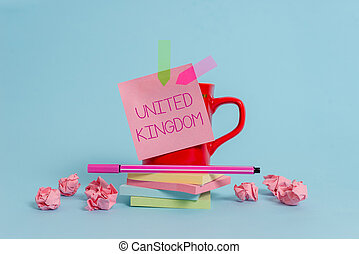 Writing note showing United Kingdom. Business photo showcasing Island country located off the northwestern coast of Europe Coffee cup pen note banners stacked pads paper balls pastel background.