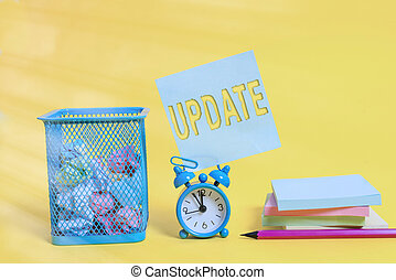 Writing note showing Update. Business photo showcasing Make something more modern Adding new facts Changing its design Alarm clock pencil note paper balls container pads colored background.
