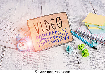 Writing note showing Video Conference. Business photo showcasing showing in remote places hold facetoface meetings Notepaper on wire in between computer keyboard and sheets.