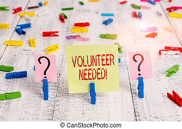 Writing note showing Volunteer Needed. Business photo showcasing asking demonstrating to work for organization without being paid Crumbling sheet with paper clips placed on the wooden table.