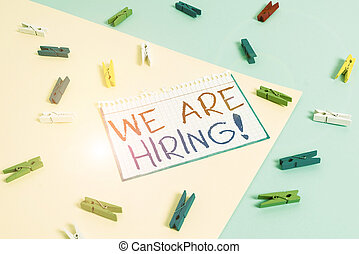 Writing note showing We Are Hiring. Business photo showcasing recently you employ someone or pay someone to do particular job Colored clothespin paper reminder with yellow blue background.