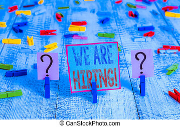 Writing note showing We Are Hiring. Business photo showcasing recently you employ someone or pay someone to do particular job Crumbling sheet with paper clips placed on the wooden table.