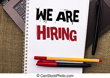 Writing note showing  We Are Hiring. Business photo showcasing Talent Hunting Job Position Wanted Workforce HR Recruitment written on Notebook Book placed on Laptop with jute background Pens