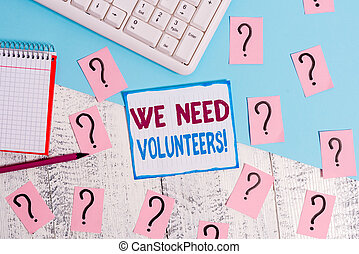 Writing note showing We Need Volunteers. Business photo showcasing someone who does work without being paid for it Writing tools and scribbled paper on top of the wooden table.
