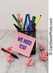 Writing note showing We Need You. Business photo showcasing asking someone to work together for certain job or target Writing equipment and paper scraps with blank sheets on the wooden desk.