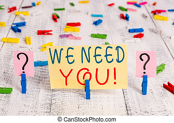 Writing note showing We Need You. Business photo showcasing asking someone to work together for certain job or target Crumbling sheet with paper clips placed on the wooden table.