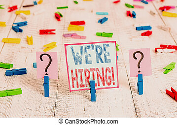 Writing note showing We Re Hiring. Business photo showcasing recently employ someone or pay someone to do particular job Crumbling sheet with paper clips placed on the wooden table.