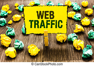 Writing note showing Web Traffic. Business photo showcasing Amount of data sent and received by visitors to a website Clothespin holding yellow note paper crumpled papers several tries.