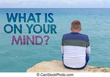 Writing note showing  What Is On Your Mind Question. Business photo showcasing Open minded thinks of intellectual innovation Man sitting sand watching beach Message Relax reflection intention.