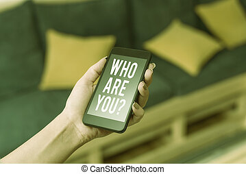 Writing note showing Who Are You Question. Business photo showcasing asking about someone identity or demonstratingal information woman using smartphone and technological devices inside the home.