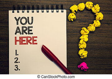 Writing note showing You Are Here. Business photo showcasing This is your location reference point global positioning system written on notepad red pen yellow paper lump question on wooden table.