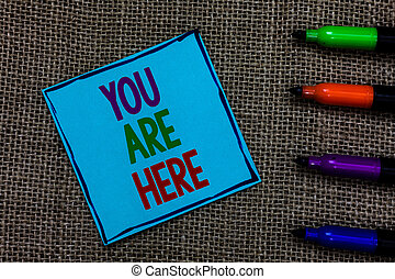 Writing note showing You Are Here. Business photo showcasing This is your location reference point global positioning system Blue paper on written letters besides color pens on black sack.