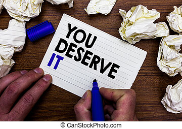 Writing note showing You Deserve It. Business photo showcasing Reward for something well done Deserve Recognition award Hand holding marker write words paper lob scatter around woody desk.