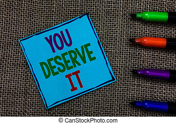 Writing note showing You Deserve It. Business photo showcasing Reward for something well done Deserve Recognition award Blue paper on written letters besides color pens on black sack.