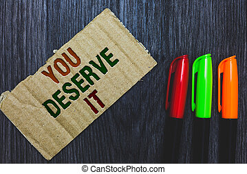 Writing note showing You Deserve It. Business photo showcasing Reward for something well done Deserve Recognition award Cardboard with letters on grey wooden desk colorful pens laid rank.