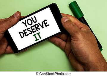 Writing note showing You Deserve It. Business photo showcasing Reward for something well done Deserve Recognition award Human hand hold iPhone with texts touched green marker.