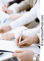 Writing notes - Business people sitting in a row and writing...