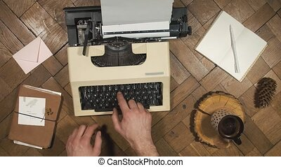 Writing on an old typewriter. Man's hand prints on a...