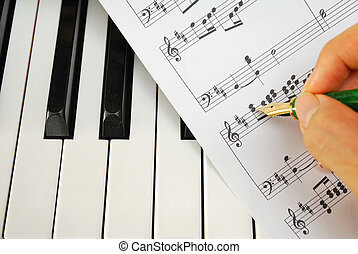 Composing music and writing on music score on a black and white piano keyboard. For concepts like music and creativity.