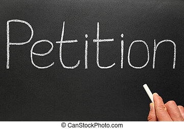 Writing Petition with white chalk on a blackboard.