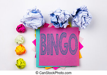 Writing text showing Bingo written on sticky note in office with screw paper balls. Business concept for Lettering Gambling to Win Price Success on the white isolated background.