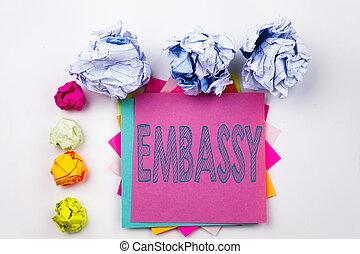 Writing text showing Embassy written on sticky note in office with screw paper balls. Business concept for Tourist Visa Application on the white isolated background.