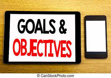 Writing text showing Goals Objectives. Business concept for Plan Success Vision Written on tablet laptop, wooden background with sticky note, coffee and pen
