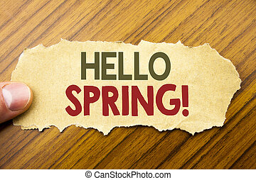Writing text showing Hello Spring . Business concept for Summer Time Welcoming written on note paper on the wooden background with human finger. Vintage style.